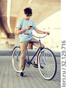 man with smartphone and earphones on bicycle. Стоковое фото, фотограф Syda Productions / Фотобанк Лори