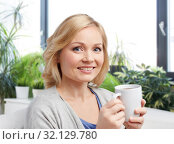 Купить «smiling woman with cup of tea or coffee at home», фото № 32129780, снято 27 ноября 2015 г. (c) Syda Productions / Фотобанк Лори