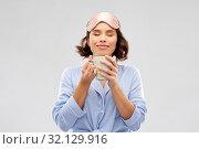Купить «woman in pajama and sleeping mask drinking coffee», фото № 32129916, снято 6 марта 2019 г. (c) Syda Productions / Фотобанк Лори