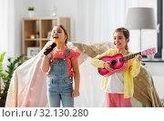 Купить «girls with guitar and microphone playing at home», фото № 32130280, снято 18 февраля 2018 г. (c) Syda Productions / Фотобанк Лори