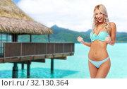 Купить «happy young woman in bikini doing fist pump», фото № 32130364, снято 20 апреля 2017 г. (c) Syda Productions / Фотобанк Лори