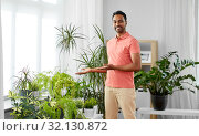 indian man taking care of houseplants at home. Стоковое фото, фотограф Syda Productions / Фотобанк Лори