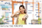 Купить «woman making phone call gesture over foreign words», фото № 32130972, снято 11 мая 2019 г. (c) Syda Productions / Фотобанк Лори