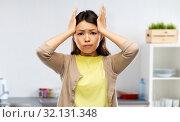 Купить «stressed asian woman holding to head at kitchen», фото № 32131348, снято 11 мая 2019 г. (c) Syda Productions / Фотобанк Лори