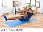 indian man making abdominal exercises at home. Стоковое фото, фотограф Syda Productions / Фотобанк Лори