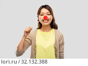Купить «happy asian woman with red clown nose», фото № 32132388, снято 11 мая 2019 г. (c) Syda Productions / Фотобанк Лори