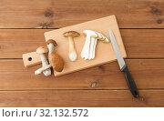 Купить «edible mushrooms, kitchen knife and cutting board», фото № 32132572, снято 13 сентября 2018 г. (c) Syda Productions / Фотобанк Лори