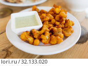 Купить «close up of cauliflower pakora with dip sauce», фото № 32133020, снято 2 мая 2017 г. (c) Syda Productions / Фотобанк Лори