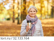 Купить «old woman with hot drink in tumbler at autumn park», фото № 32133164, снято 14 октября 2018 г. (c) Syda Productions / Фотобанк Лори