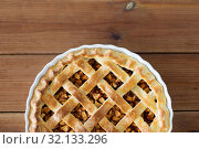 Купить «close up of apple pie in mold on wooden table», фото № 32133296, снято 23 августа 2018 г. (c) Syda Productions / Фотобанк Лори
