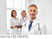Купить «smiling doctor in white coat at hospital», фото № 32133672, снято 6 июля 2013 г. (c) Syda Productions / Фотобанк Лори