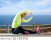 Купить «woman stretching on exercise mat over sea», фото № 32133916, снято 19 июня 2013 г. (c) Syda Productions / Фотобанк Лори