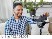 Купить «indian male video blogger adjusting camera at home», фото № 32134004, снято 21 апреля 2019 г. (c) Syda Productions / Фотобанк Лори