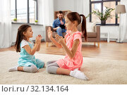 Купить «happy little sisters playing clapping game at home», фото № 32134164, снято 31 марта 2019 г. (c) Syda Productions / Фотобанк Лори