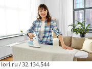 Купить «asian woman or housewife ironing bed linen at home», фото № 32134544, снято 13 апреля 2019 г. (c) Syda Productions / Фотобанк Лори
