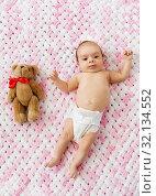 Купить «baby girl in diaper lying with teddy on blanket», фото № 32134552, снято 23 мая 2019 г. (c) Syda Productions / Фотобанк Лори