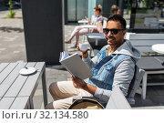 Купить «man reading book and drinking coffee at city cafe», фото № 32134580, снято 22 июня 2019 г. (c) Syda Productions / Фотобанк Лори