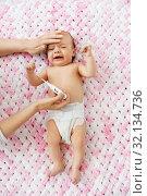 Купить «mother measuring temperature of crying baby», фото № 32134736, снято 23 мая 2019 г. (c) Syda Productions / Фотобанк Лори