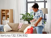 Купить «happy woman picking clothes for laundry at home», фото № 32134932, снято 7 апреля 2019 г. (c) Syda Productions / Фотобанк Лори