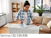Купить «african american woman ironing bed linen at home», фото № 32134936, снято 7 апреля 2019 г. (c) Syda Productions / Фотобанк Лори