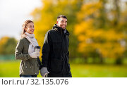 Купить «couple with tumbler walking along autumn park», фото № 32135076, снято 29 сентября 2018 г. (c) Syda Productions / Фотобанк Лори