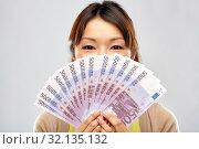 Купить «asian woman with hundreds of euro money banknotes», фото № 32135132, снято 11 мая 2019 г. (c) Syda Productions / Фотобанк Лори
