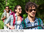 Купить «group of friends with backpacks hiking in forest», фото № 32135156, снято 15 июня 2019 г. (c) Syda Productions / Фотобанк Лори