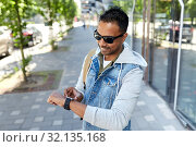 Купить «indian man with smart watch and backpack in city», фото № 32135168, снято 22 июня 2019 г. (c) Syda Productions / Фотобанк Лори