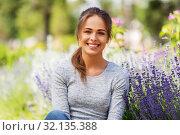 Купить «young woman with flowers at summer garden», фото № 32135388, снято 12 июля 2019 г. (c) Syda Productions / Фотобанк Лори
