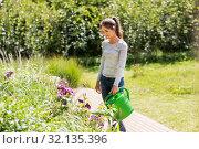 Купить «young woman watering flowers at garden», фото № 32135396, снято 12 июля 2019 г. (c) Syda Productions / Фотобанк Лори