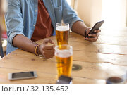 man with smartphone drinking beer at bar or pub. Стоковое фото, фотограф Syda Productions / Фотобанк Лори