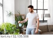 Купить «man spraying houseplants with water at home», фото № 32135508, снято 22 мая 2019 г. (c) Syda Productions / Фотобанк Лори