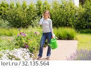 Купить «young woman watering flowers at garden», фото № 32135564, снято 12 июля 2019 г. (c) Syda Productions / Фотобанк Лори
