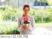 Купить «young woman with cyclamen flowers at summer garden», фото № 32135708, снято 12 июля 2019 г. (c) Syda Productions / Фотобанк Лори