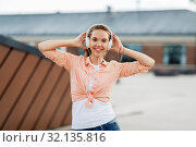 Купить «happy teenage girl with headphones in city», фото № 32135816, снято 20 июня 2019 г. (c) Syda Productions / Фотобанк Лори
