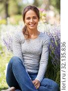 Купить «young woman with flowers at summer garden», фото № 32135836, снято 12 июля 2019 г. (c) Syda Productions / Фотобанк Лори