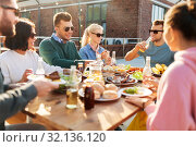 friends having dinner or bbq party on rooftop. Стоковое фото, фотограф Syda Productions / Фотобанк Лори