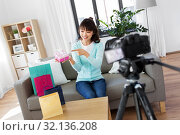 Купить «asian female blogger with gift bag recording video», фото № 32136208, снято 13 апреля 2019 г. (c) Syda Productions / Фотобанк Лори