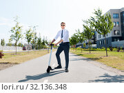 Купить «young businessman riding electric scooter outdoors», фото № 32136348, снято 1 августа 2019 г. (c) Syda Productions / Фотобанк Лори