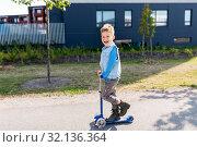 Купить «happy little boy riding scooter in city», фото № 32136364, снято 1 августа 2019 г. (c) Syda Productions / Фотобанк Лори