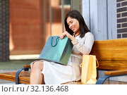 Купить «asian woman with shopping bags on bench in city», фото № 32136468, снято 13 июля 2019 г. (c) Syda Productions / Фотобанк Лори