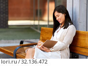 Купить «asian woman with notebook or sketchbook on bench», фото № 32136472, снято 13 июля 2019 г. (c) Syda Productions / Фотобанк Лори