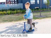 Купить «happy little boy riding scooter in city», фото № 32136508, снято 1 августа 2019 г. (c) Syda Productions / Фотобанк Лори