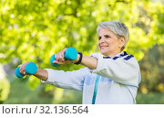 Купить «senior woman with dumbbells exercising at park», фото № 32136564, снято 28 июня 2019 г. (c) Syda Productions / Фотобанк Лори