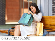 Купить «asian woman with shopping bags on bench in city», фото № 32136592, снято 13 июля 2019 г. (c) Syda Productions / Фотобанк Лори