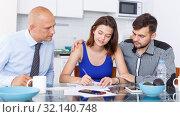 Купить «Smiling young man and wife signing agreement papers with social worker», фото № 32140748, снято 6 июля 2018 г. (c) Яков Филимонов / Фотобанк Лори