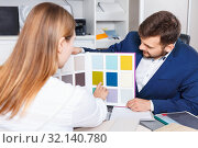 Купить «Competent seller in showroom helping young female client to choose furniture materials for her apartment», фото № 32140780, снято 9 апреля 2018 г. (c) Яков Филимонов / Фотобанк Лори