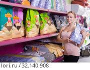 Купить «Woman customer choosing food for pets», фото № 32140908, снято 6 декабря 2019 г. (c) Яков Филимонов / Фотобанк Лори
