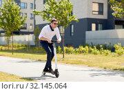 Купить «young businessman riding electric scooter outdoors», фото № 32145064, снято 1 августа 2019 г. (c) Syda Productions / Фотобанк Лори