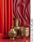 Купить «Copperware in oriental style on a red background with theatrical design.», фото № 32145240, снято 29 января 2019 г. (c) Olesya Tseytlin / Фотобанк Лори